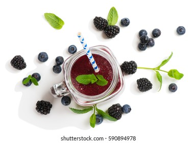 Top view of smoothie of summer berries ( blueberry and blackberry ) in mason jars with straws isolated on white background.