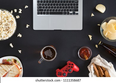 Top view of Snacks and unhealthy food with laptop on black background, gamer concept