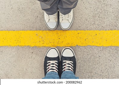 Top View of Sneakers from above, Male and female feet in sneakers, standing at dividing frontier line.
