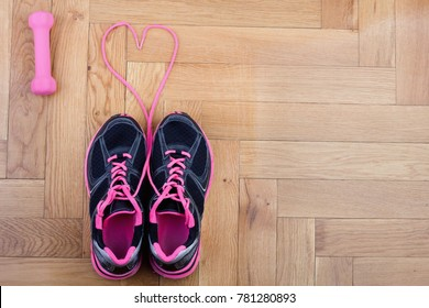 Top view of sneakers and dumbbell forming emotion love. Sport and healthy lifestyle concept