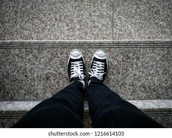 top view of sneakers standing on stairs,Feet on the stairs.