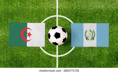 Top view soccer ball with Algeria vs. Guatemala flags match on green football field.