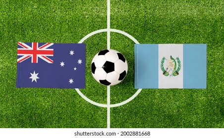 Top view soccer ball with Australia vs. Guatemala flags match on green football field.