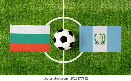 Top view soccer ball with Bulgaria vs. Guatemala flags match on green football field