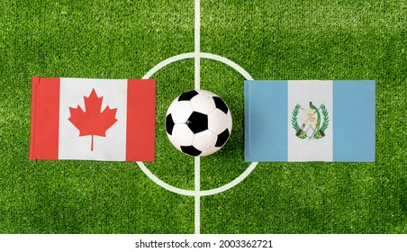 Top view soccer ball with Canada vs. Guatemala flags match on green football field.