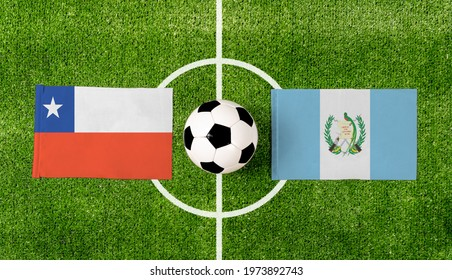 Top view soccer ball with Chile vs. Guatemala flags match on green football field.