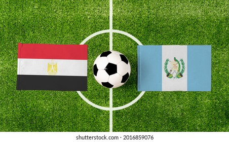 Top view soccer ball with Egypt vs. Guatemala flags match on green football field