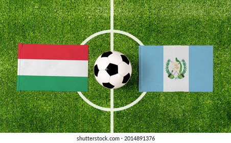 Top view soccer ball with Hungary vs. Guatemala flags match on green football field