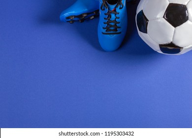 Top view of soccer ball and pair of soccer football sports shoes on blue background