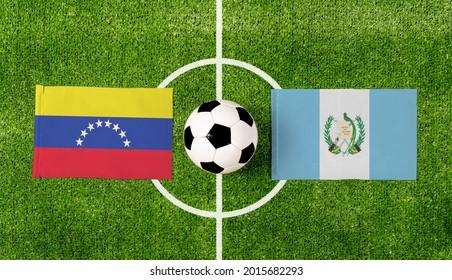 Top view soccer ball with Venezuela vs. Guatemala flags match on green football field