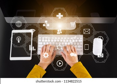 top view Social media and Marketing virtual icons screen concept.close up of businessman typing keyboard with laptop computer, tablet on black desk in modern office