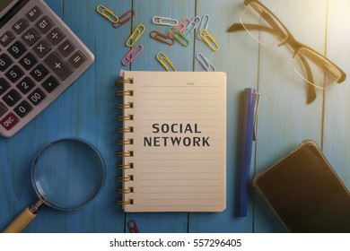 Top view of SOCIAL NETWORK written on the notebook,magnifier glass,calculator,smart phone,pen and glasses on blue wooden desk.business concept.