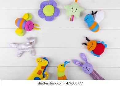 top view with soft baby toys on wooden background