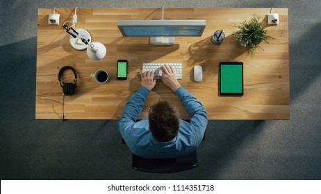 Top View of a Software Engineer Working at His Desktop Computer Sitting in His Creative Office. Lying on the Table: Smartphone, Tablet Computer, Headphones.