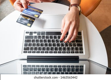 Top view of someone hand holding credit card during using laptop for online shopping. Online shopping is the process of buying goods and services from merchants over the Internet.