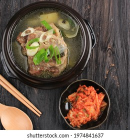 Top View Sop Buntut Gori Gomtang (Sokkori Gomtang) or Korean Beef Oxtail Stew  Soup, Served in the Black Korean Bowl with Kimchi and Sliced Green Onion - Shutterstock ID 1974841637
