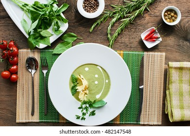 Top view of soup with zucchini in a white plate on a wooden table