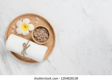 Top view of Spa products in wooden tray in round shape on white marble background. Towel, Salt, Plumeria Flower, Bowl with Copy space.