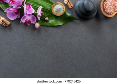 Top view of spa setting with hot stones and pink salt. High angle view of orchids with green leaf on blackboard with stacked hot stone for massage treatment. Luxury and elegant spa set with copy space
