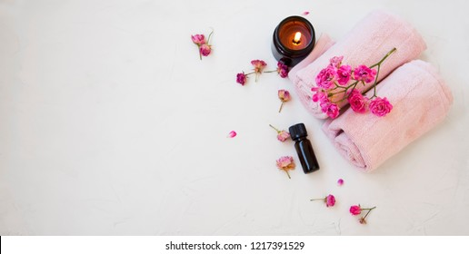 Top view of spa still life setting with scented candle, towels, roses and rose oil, spa and aromatherapy skincare treatment