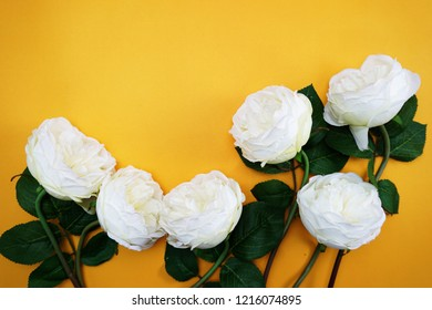 top view space copy with artificial peony flowers bouquet on yellow background
