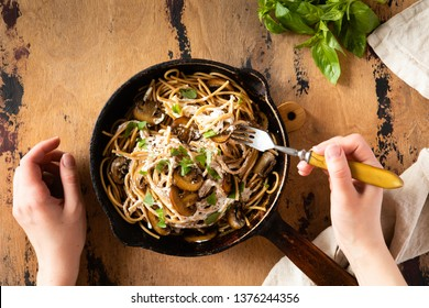 Top view of Spaghetti Pasta with Mushrooms and cream sauce on wooden rustic background. Classic italian pasta with champignon mushroom in vintage frying pan.