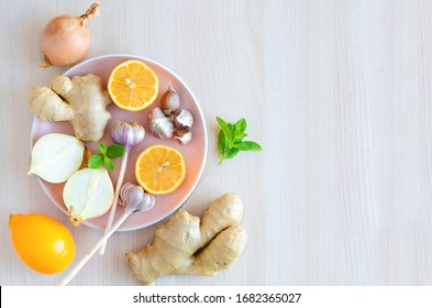top view of spice set, vegetables garlic, ginger, onions, lemon to boosting immunity, treat colds, viruses, flu on light background, copy space. alternative medicine. soft focus. eco products