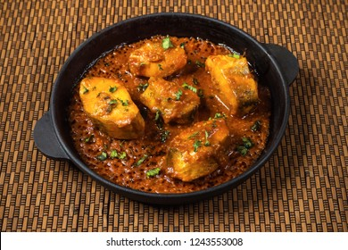Top view of spicy and hot Bengali fish curry. Indian food. Fish curry with red chili, curry leaf, coconut milk. Asian cuisine.