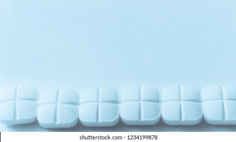 Top view of the Spilled white pills on the blue surface