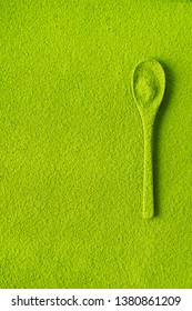 Top view of a spoon strewed with green tea Matcha on the background of texture of powder maccha with copy space.