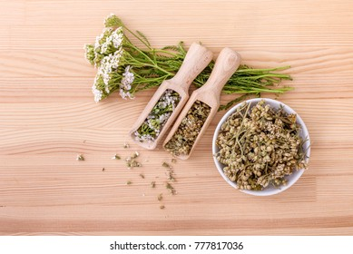 Top view of spoons and bowl with fresh and dried flowers and leaves of yarrow with a wooden background