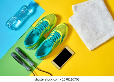 Top view of sport shoes, mobile smartphone, skipping rope, towel and water on colorful blue, yellow and green backgroundon, copy space. Top view, flat lay. Healthy lifestyle concept, overhead shot