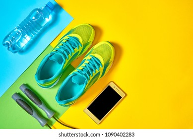 Top view of sport shoes, skipping rope, mobile cellphone and bottle of water on colorful background, copy space. Flat lay. Sport, fitness concept, healthy lifestyle