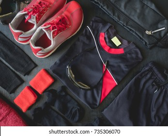 top view sport wear concept with Gym Outfit, running shoes, smartphone, Sport Sweatband and sport run accessories on black wooden background