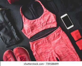 top view sport wear concept with Gym Outfit, running shoes, smartphone, Sport Sweatband and sport run accessories on black wooden background.