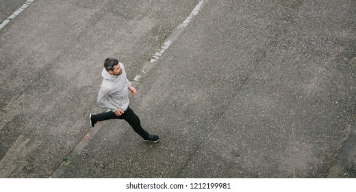 Top view of sporty man running in winter on urban asphalt. Male runner training outside.