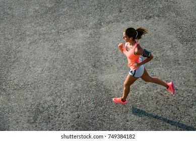 Top view of sporty young fit woman running on urban asphalt. Female athlete training outside in summer.