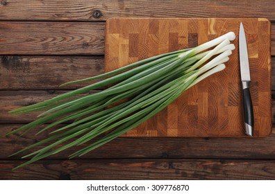 Top view of spring onions bunch ready to cutting on chopping board