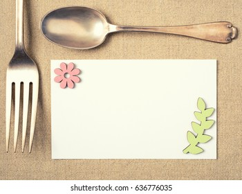Top View of A Spring Party Invitation Card with a Vintage Fork and Spoon on a Gold Lame` Place mat. There's room or space for copy, text or your words. Cross Processed with muted tone for modern style