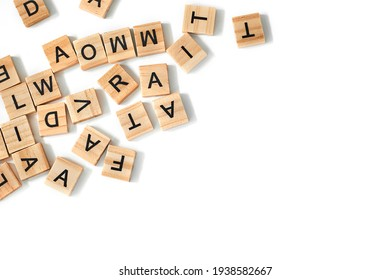 Top view of square wooden tiles with the English alphabet scattered on a white background with space for text. The concept of thinking development, grammar.