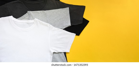 top view stack of black, grey and white (monochrome) t-shirt on yellow background with copy space, flat lay