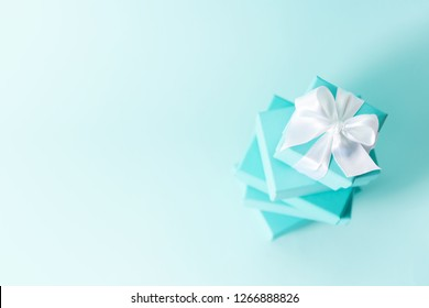 Top view of stack of boxes tied with silk ribbon, lying on each other on tiffany blue color pastel background. Gift festive selection.