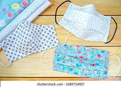 Top view Stack cotton and 3 type of DIY fabric cotton face mask on wood table. Protect saliva, cough, dust, pollution (PM2.5), Virus, Bacteria, COVID-19. Handmade. fashion concept.