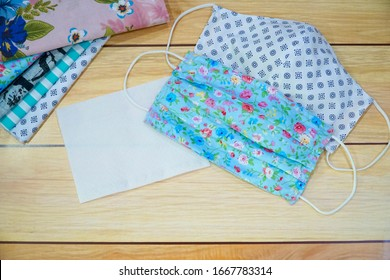 Top view of Stack cotton, white tissue paper and DIY fabric cotton face mask on wood table. Protect saliva, cough, dust, pollution (PM2.5), Virus, Bacteria, COVID-19. Handmade concept. Copy space. - Shutterstock ID 1667783314