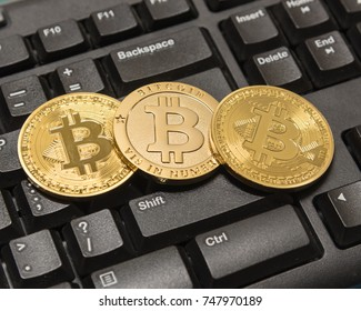 Top view stack of golden Bitcoins (Cryptocurrency) on computer keyboard.