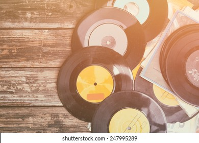 top view of stack of records over wooden table. retro style filter