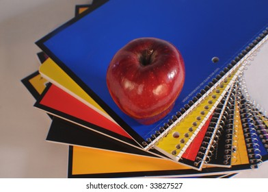 top view of a stack of spiral notebooks and an apple