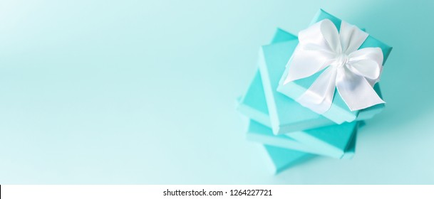 Top view of stack of Tiffany boxes tied with silk ribbon, lying on each other on tiffany blue color pastel background. Gift festive selection. long wide banner