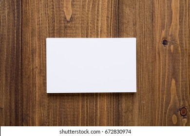 Top view of stack white business cards on dark wooden background, use for mock up branding identity