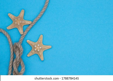 Top view starfish and rope, summer sea composition on a blue background